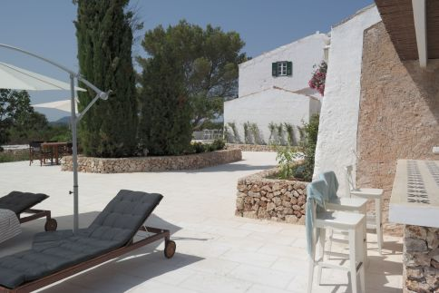 The front corner of the house taken from swimming pool and barbeque area with sunbeds and parasol.